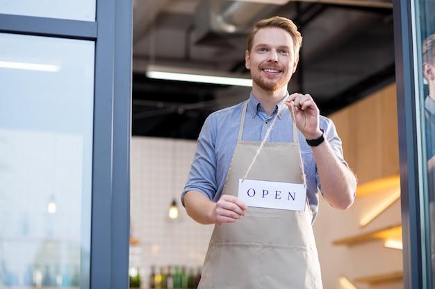 私たちの場所をご覧ください。ドアの近くに立って、彼のカフェに顧客を招待しながら笑っている幸せな格好良いフレンドリーなウェイター