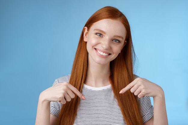 Visita il posto che ami. donna dall'aspetto gentile gentile e attraente dai capelli rossi che mostra lo spazio della copia pubblicitaria che punta il dito indice verso il basso inclinando la testa sorridente utile consiglia promo Foto Gratuite