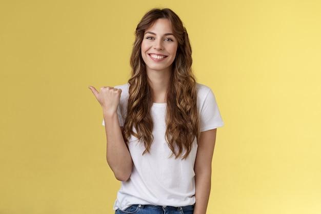 직접 방문하십시오. 쾌활한 카리스마 넘치는 잘 생긴 외향적인 소녀 긴 곱슬머리를 보여주는 곳에서 좋은 헤어스타일을 하고 행복하게 웃고 엄지손가락을 왼쪽으로 가리키며 프로모션 노란색 배경을 소개합니다.