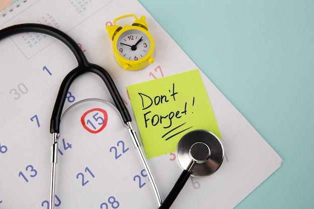 Посетите «напоминание о докторе» на стикере, желтом будильнике и стетоскопе в календаре.