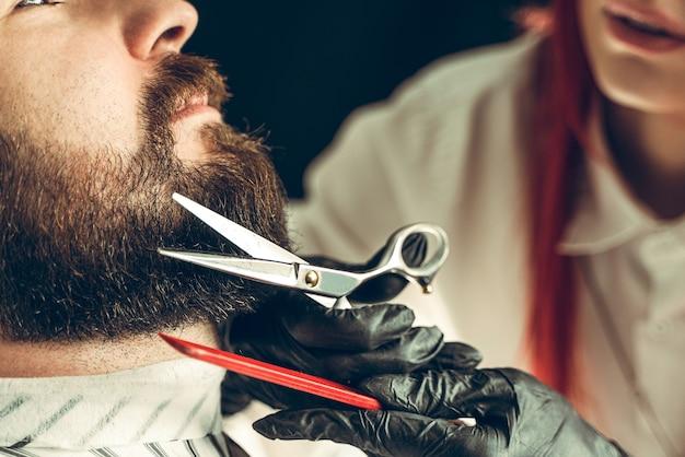 Посещение парикмахерской. мастер стригет бороду ножницами