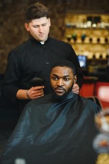 スタイリッシュな理髪店で理髪店アフリカ系アメリカ人男性を訪問