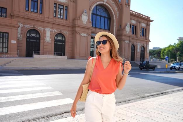 바리 방문. 이탈리아 바리에서 걷고 있는 행복한 웃고 있는 젊은 패션 여성의 초상화.