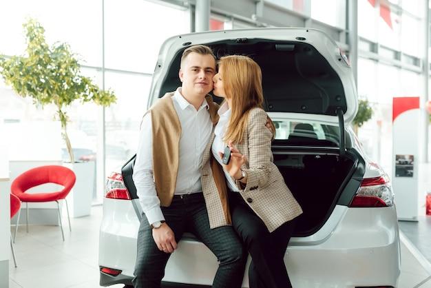 Посещение автосалона. красивая пара держит ключ от своей новой машины и улыбается, девушка целует мужа в щеку