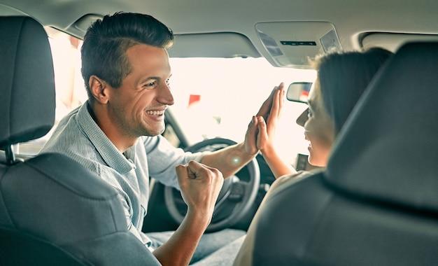 自動車販売店を訪問。美しいカップルがカメラを見て、新しい車に座っている間、お互いに5を与えます