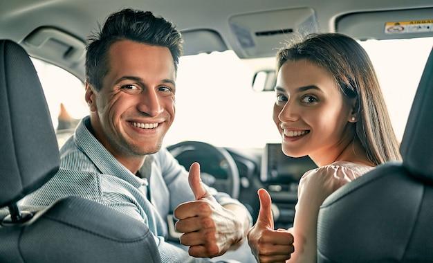 自動車販売店を訪問。美しいカップルがカメラを見て、新しい車に座っている間親指を表示します