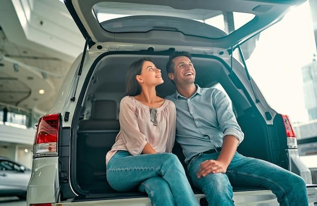 Посещение автосалона. красивая пара сидит в открытом багажнике своей новой машины и улыбается.