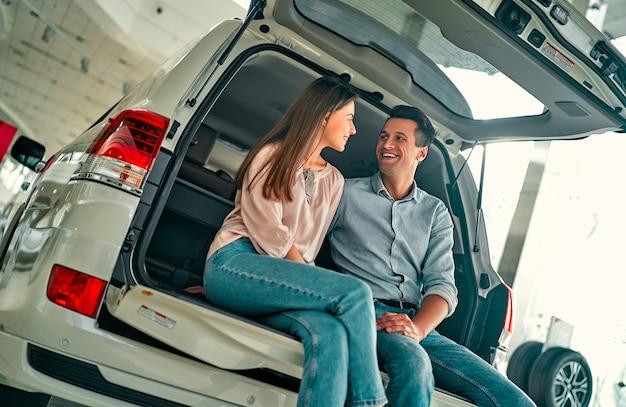自動車販売店を訪問。美しいカップルが新しい車の開いたトランクに座って笑っています。