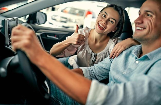 自動車販売店を訪問。美しいカップルが新しい車に座って笑っています。親指を立てて、車を買って幸せな美しい女性。
