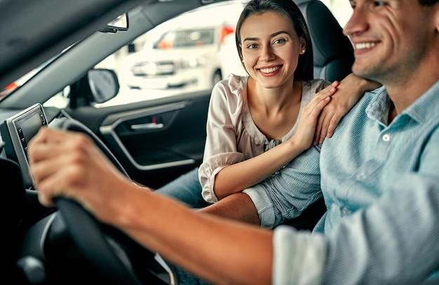 自動車販売店を訪問。美しいカップルが新しい車に座って笑っています。