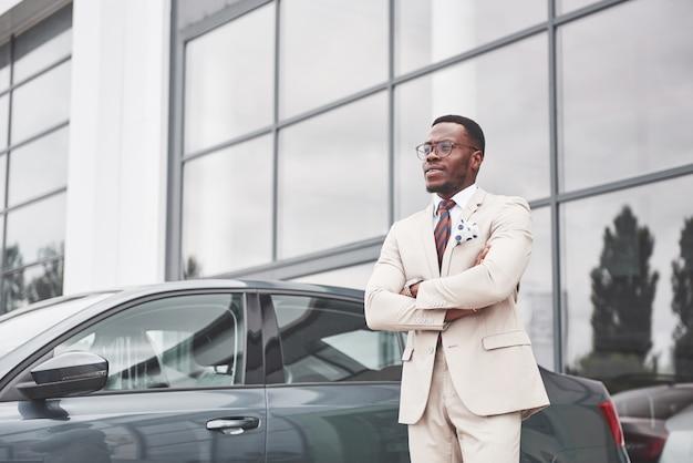 カーディーラー訪問。車の近くのスーツでカジュアルな黒のビジネスマン。