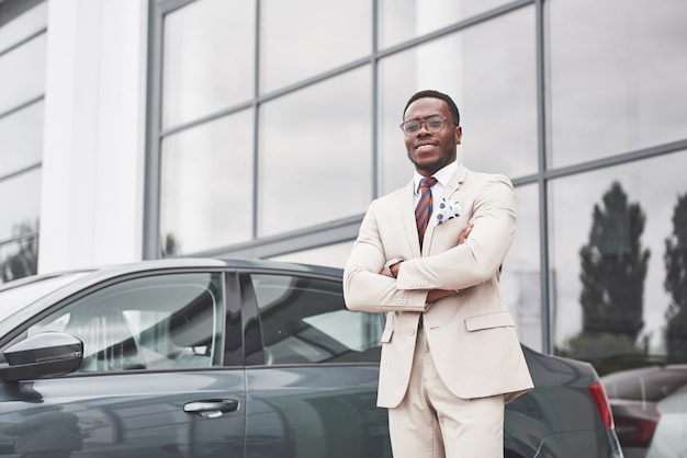 Visiting car dealership. casual black business man in a suit near the car.