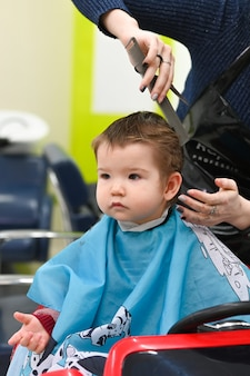 Visiting a child at the hairdresser. the first haircut of the child at the hairdresser. baby haircut toddler.