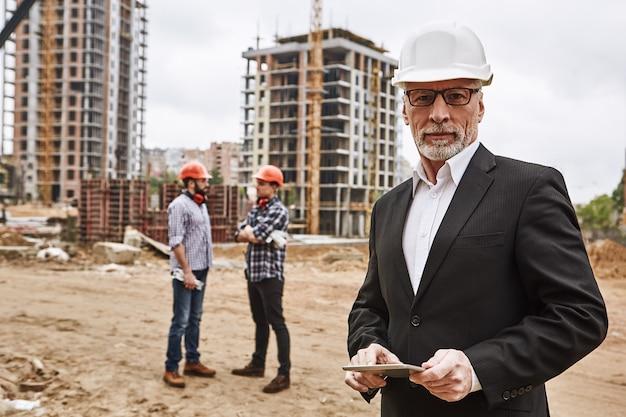 Посещение строительной площадки портрет уверенного пожилого инженера-строителя в классическом костюме и