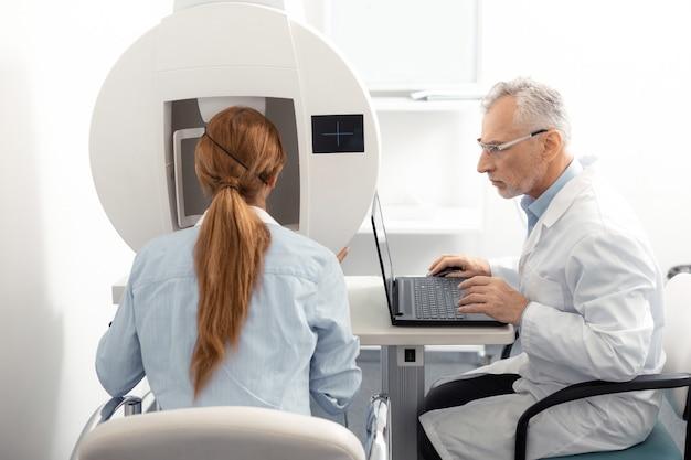 Посещение офтальмолога. рыжая женщина в синей рубашке посещает окулиста после рабочего дня