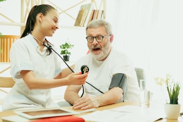 L'infermiera in visita o l'ospite sanitario che si prende cura dell'uomo anziano