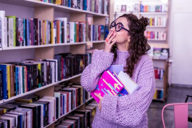 公共図書館を訪問する。教育のための読書を選択しながら本棚の間で時間を過ごす興奮したハンサムな女の子