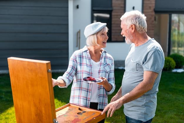 방문하는 아내. 사랑하는 수염 난 남편이 와서 정원에서 그리는 그의 아름다운 매력적인 아내를 방문