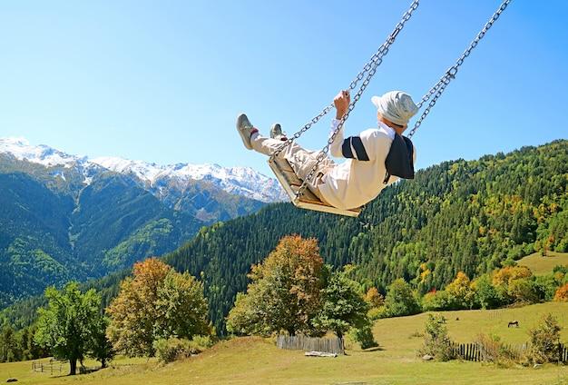 방문자는 코카서스 산맥의 멋진 가을 전망과 함께 그네를 즐깁니다.