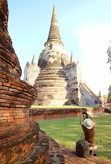 タイのアユタヤ歴史公園にあるワットプラシーサンペットの有名な歴史的塔の写真を撮る訪問者