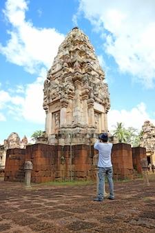 Посетитель фотографирует руины главной башни древнего кхмерского храма сдок кок том, таиланд
