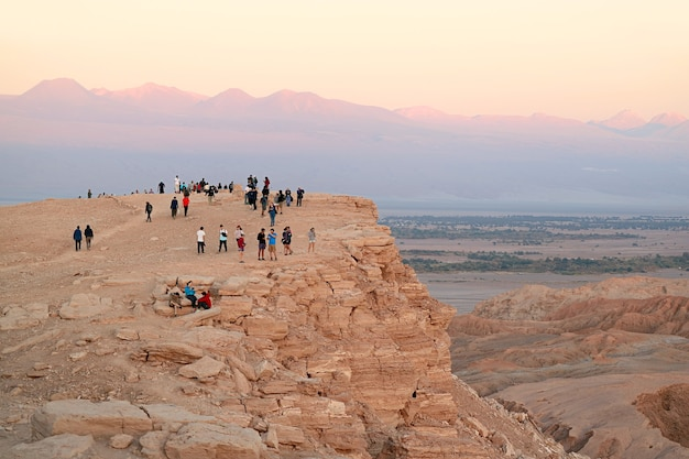 Visitors on the cliff waiting for sunset at valle de la luna or moon valley in atacama desert chile
