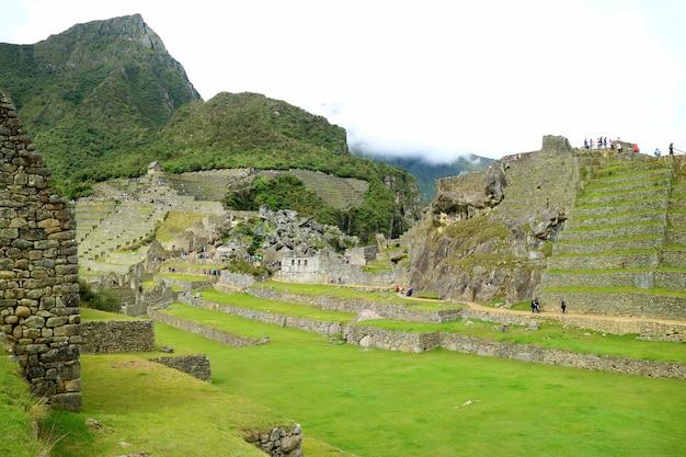 Visitors enjoy exploring inside the remains of machu picchu inca citadel, cusco, peru, south america