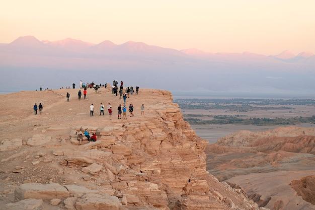 아타카마 사막 칠레의 발레 드 라 루나 또는 문 밸리에서 일몰을 기다리는 절벽 위의 방문객