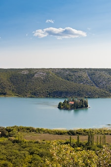 Христианский монастырь висовац на острове в национальном парке крка, хорватия. с высоты птичьего полета