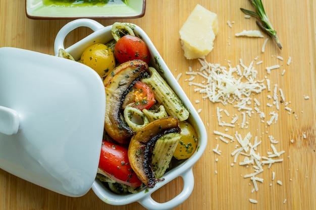 Vista cerrada ensalada de pasta con vegetales en un tazon blanco con queso