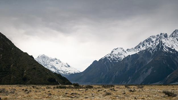 뉴질랜드 쿡 산 눈으로 덮인 봉우리가 있는 폭풍우가 다가오는 동안 고산 계곡의 비스타