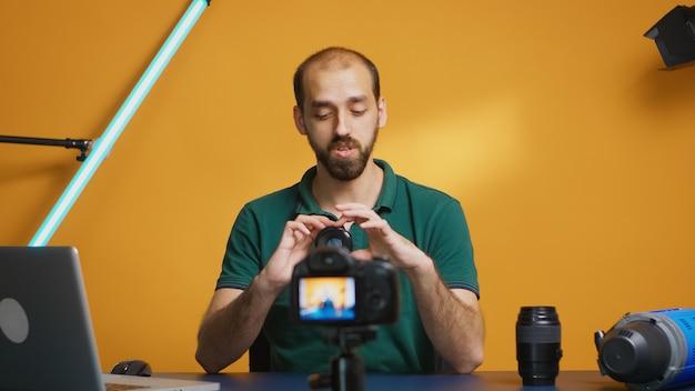 Artista visivo che registra il confronto dell'obiettivo della fotocamera per il suo vlog. tecnologia dell'obiettivo della fotocamera registrazione digitale creatore di contenuti influencer social media, studio professionale per podcast, vlogging e blog