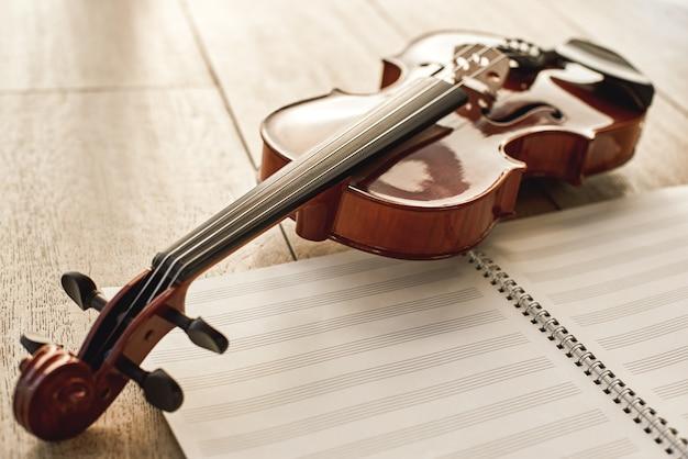 Визуальная красота классического инструмента. крупным планом вид коричневой красивой скрипки, лежащей на листах для нот над деревянным полом. музыкальные инструменты. музыкальное оборудование. музыкальный фон