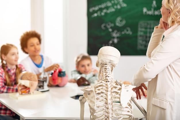 시각 자료. 생물학 교사 근처에 서있는 인간 골격의 선택적 초점