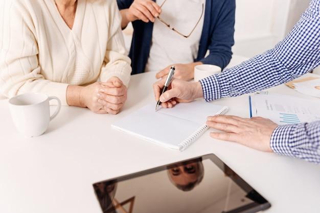집 프로젝트 시각화. 재능있는 영감을 얻은 유용한 부동산 중개인이 은퇴 한 고객과 함께 집안의 프로젝트를 시연하고 그림을 보여줍니다.