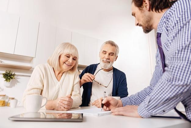 이상적인 집 레이아웃 시각화. 집의 프로젝트를 시연하고 그림을 그리는 동안 은퇴 한 고객과 함께 일하는 재능있는 긍정적이고 활기찬 부동산 중개인