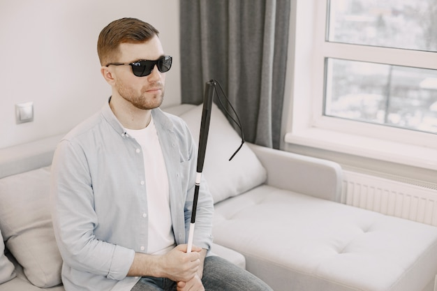 Visually impaired man sitting on the couch with stick