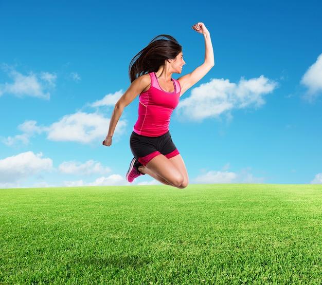 活気に満ちたアスレチックな女の子が牧草地で非常に高くジャンプします