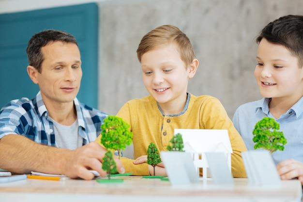 Жизненно важная помощь. очаровательный молодой человек сидит за столом рядом со своими сыновьями и помогает им в их экологическом проекте, делится своим опытом в этой области.