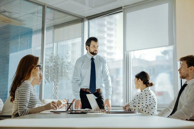 重要な問題。テーブルの先頭に立って同僚とミーティングを行い、重要な問題について話し合うハンサムな若い男