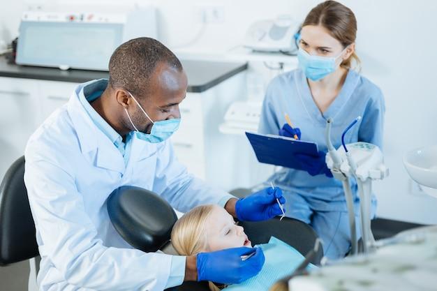 重要なメモ。小さな女の子の口腔の徹底的な検査を行っている間、歯科医の観察のメモをとっている魅力的な若い女性看護師