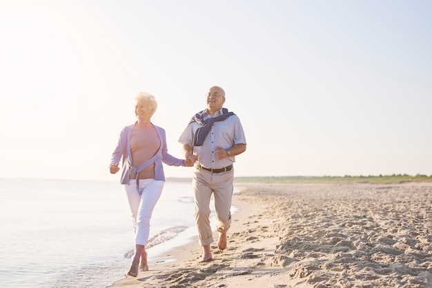 Vital seniors on the beach. senior couple in the beach, retirement and summer vacation concept