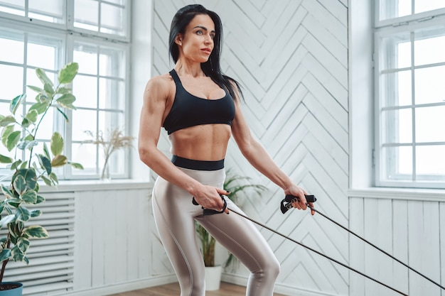 活力とスポーティーなライフスタイル。成熟した女性のボディービルダーは、窓のある明るい部屋で輪ゴムを使って運動をします。