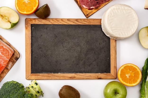 白い背景で隔離の食品と黒板のモックアップのビタミンa