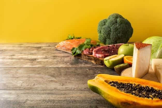 木製のテーブルと黄色の背景に果物、野菜、チーズ、魚、肉を含む食品中のビタミンa