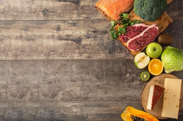 木製のテーブルに果物、野菜、チーズ、魚、肉を含む食品中のビタミンa