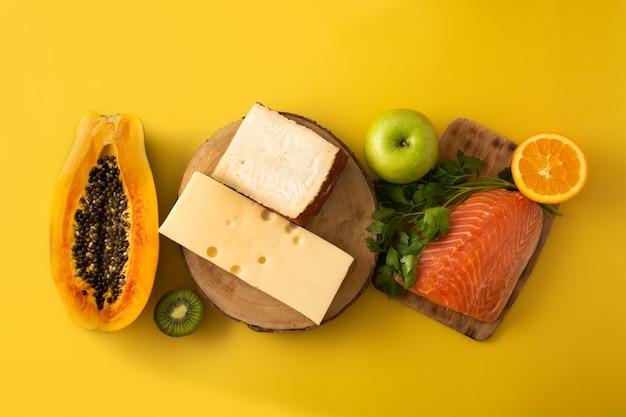 黄色の背景に果物、野菜、チーズ、魚、肉を含む食品中のビタミンa
