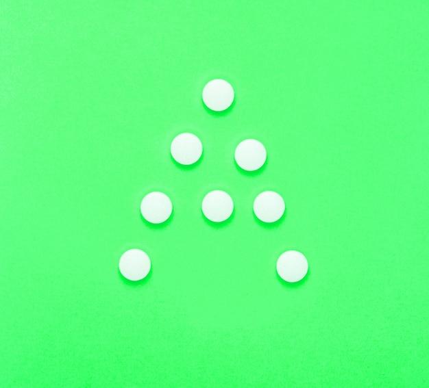 ビタミンa。緑の背景に白い錠剤からの手紙a。ミニマルな医療コンセプト。上面図。