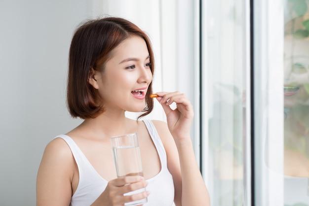 비타민과 보충제. 노란색 생선 기름 알 약을 복용 하는 아름 다운 젊은 여자의 근접 촬영입니다.