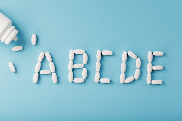 Vitamin a b c d e tablets fell out of a white jar on a blue background. the letter a b c d e is an inscription. the concept of immune protection, antiviral prevention. food additives. free space